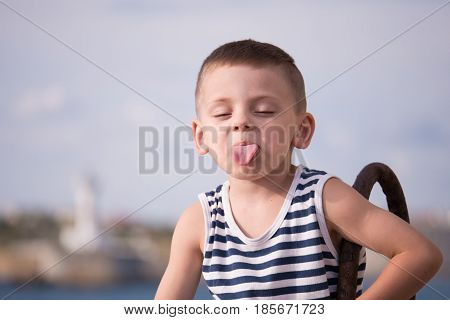 Funny boy in sailor stripes vest showing tongue closing his eyes