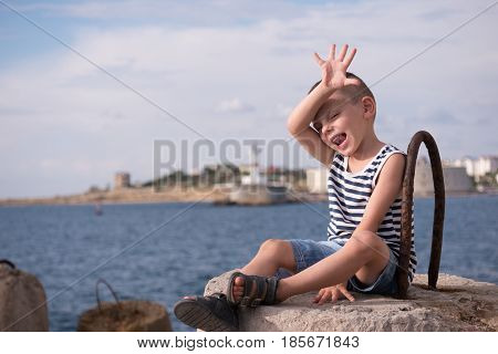 Funny little boy in sailor vest waving his hand while sitting on a breakwater on the background of the sea and lighthouse