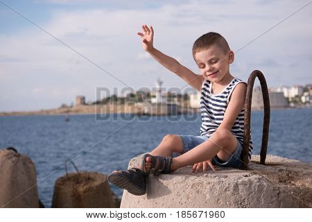happy little boy in sailor vest waving his hand while sitting on a breakwater on the background of the sea and lighthouse