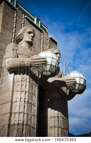 Helsinki railway station granite statues holding lamps