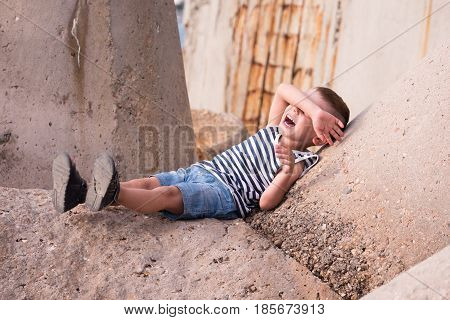 laughing little boy in a vest and shorts lies on a concrete breakwater in port covering his eyes with his hand