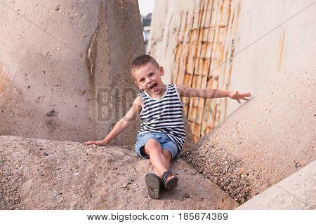 happy little boy in sailor stripes singlet and jean shorts sitting on concrete breakwater