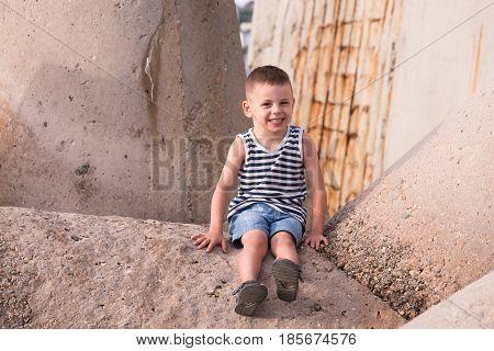 Happy smiling little boy in sailor vest sitting on breakwater in port