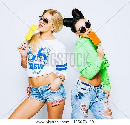 Pretty brunette, blond girls, bright makeup, pink lips. Enjoys ice cream. Have fun and smile. Dressed in bright, fashionable shorts, jeans T-shirt and hoodie, in sunglasses. Indoor. Gelato. Eskimo pie.