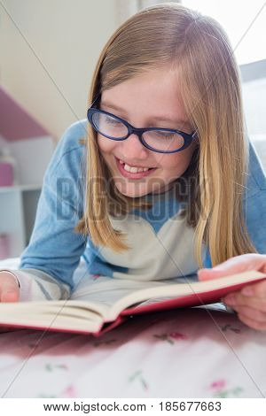 Young Girl Lying On Bed Reading Book
