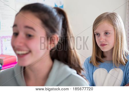Young Girl Staring At Disliked Friend From Behind