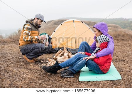 Side view of smiling mother embracing little son and looking at young man holding bottle with liquid for kindling fire. Happy young family sitting near tent