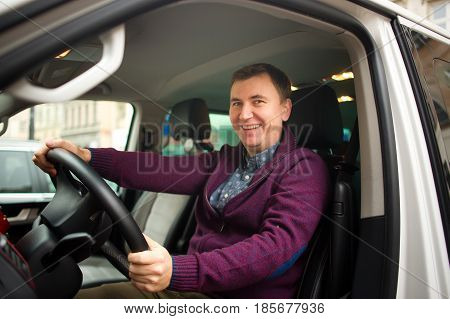 Young man is sitting at the wheel of a car. City parking. Man has a good mood.