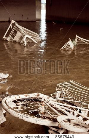 a bicycle and two shopping carts are buried deep in the mud