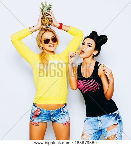 Summer portrait of two pretty blond and brunette girl friends having fun with pineapple, chips. Singing with sunglasses and smiling. Casual style, bright makeup, pink lips. White background, not isolated. Indoor. Bestis.
