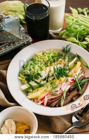 Traditional Russian summer Cold Soup Okroshka with sausage, vegetables and kvass serving size in bowl and raw ingredients on wooden table