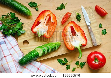 Variety of vegetables for salad on wooden kitchen board. Healthy food Clean Eating or Vegetarian concept. Overhead shot