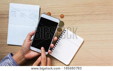 Hand Finger Press On Blank Screen Of Smart Phone For Internet Banking Wiht Background Of Coins And