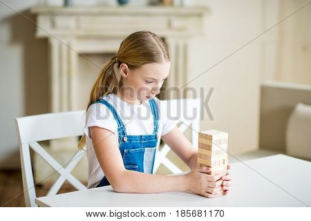 Concentrated preteen girl building tower from wooden bricks on table