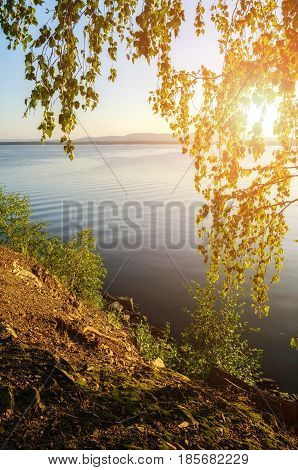 Summer sunset water landscape of Irtyash Lake in Southern Urals Russia.Summer lake in sunny evening. Sunny summer landscape of summer lake waters framed by summer trees. Sunny summer water landscape nature