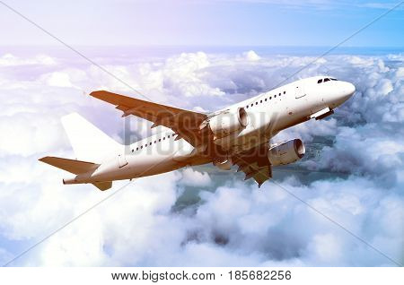 White airplane flying in the sky among white dense clouds floating over land surface. Airplane in the flight.Birds eye view of flying airplane. Airplane in the sky under sunlight.Travel background with flying airplane. Flying airplane