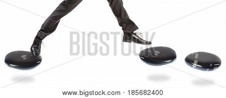 a businessman is jumping over a gap in his path.