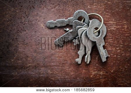 A bunch of the old metal grey small key on old grunge wooden surface