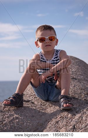 Beautiful little boy in sunglasses and sailor vest and shorts sitting on breakwater on background of the sky and the sea