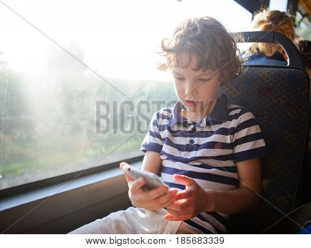 A small passenger of a city bus with a smartphone in hand. The boy sits at the window and looks with interest at the screen of the smartphone.