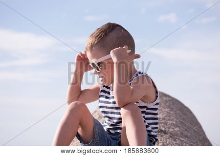 cute little boy wearing white sunglasses and sailor stripes shirt sitting on concrete breakwater
