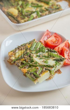 Home made frittata with green asparagus and tomato