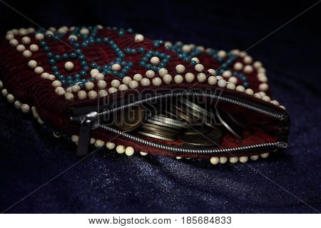 purse decorated with beads is full of gold and silver coins