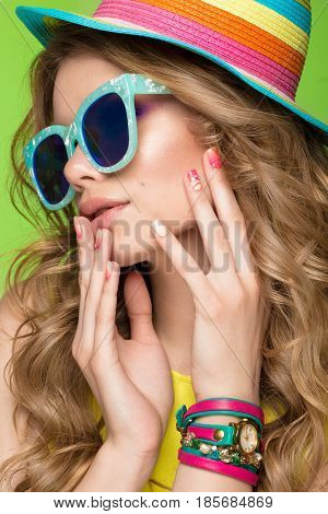 Bright cheerful girl in a summer hat, colorful make-up, curls and pink manicure. Beauty face. Photo taken in the studio.