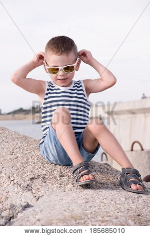 Beautiful little boy in white sunglasses and sailor vest and shorts sitting on breakwater on background of pier and the sea touching his sunglasses