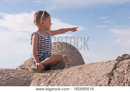 little boy with sunglasses sitting on the breakwater pointing his hand and finger into the distance