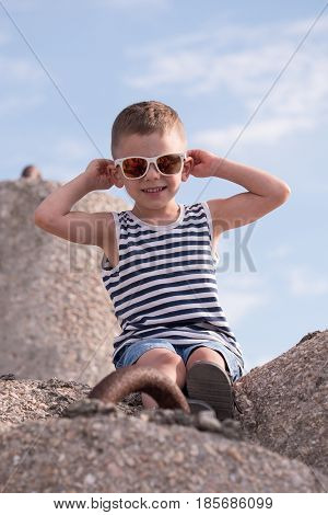 Cute smiling little boy in sunglasses and a vest sitting on a concrete breakwater