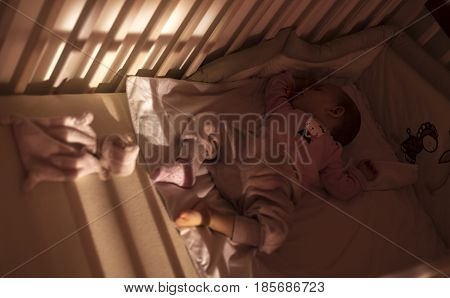 An adorable baby is asleep during the day. Bed time for kids. Bedroom and nursery interior.