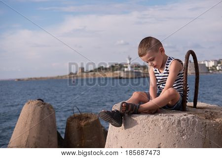 cute little boy sitting on breakwater on background of sea and shore with lighthouse