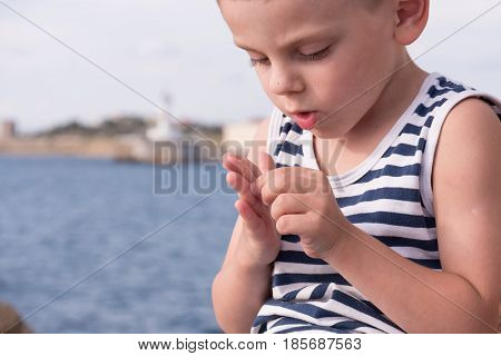 Attentive little boy wearing sailor stripes shirt gets a splinter from his finger
