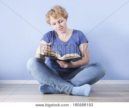 average age blond pretty woman sitting on the floor cross-legged and reading a book