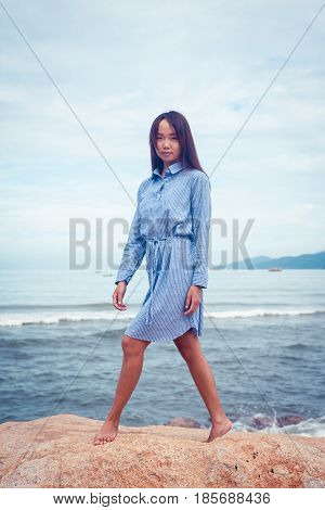 A portrait of beautiful asian woman in blue dress walking on a stone by the sea
