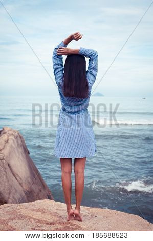 A portrait of beautiful asian woman in blue dress back stand and rise hands on a stone by the sea