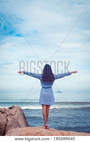 A portrait of beautiful asian woman in blue dress back stand, hands to the sides on a stone by the sea