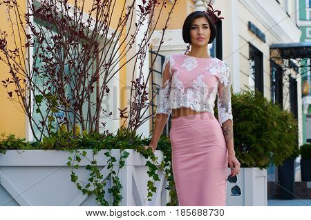 Young beautiful woman in a pink skirt and blouse on a city street