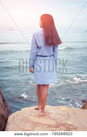 A sunny portrait of beautiful asian woman in blue dress back stand on a stone by the sea