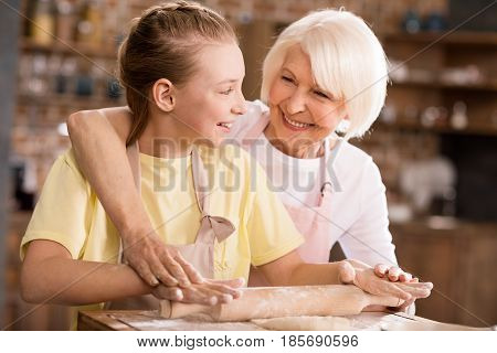 Grandmother And Grandchild Kneading Dough