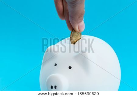 Inserting a coin into a piggy bank