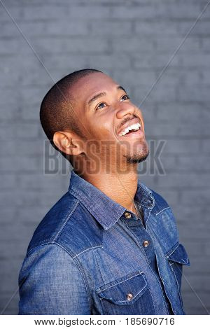 Happy Young Black Guy Laughing And Looking Up
