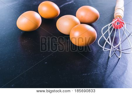 eggs and whisk on a black background