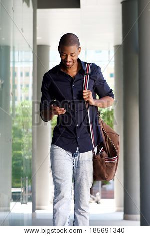 Young Black Man Walking In City With Cellphone And Bag