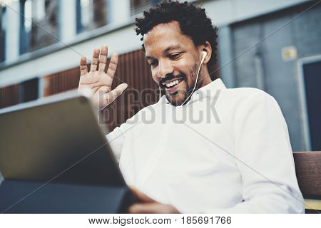 Smiling African American man in headphones making video call at sunny street on electronic touch pad, checking e-mail using Internet-enabled electronic device, calling friends via social networks