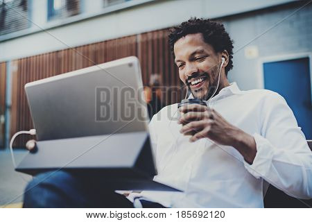 Happy African American man in earphones making video call via electronic touch pad pro with take away coffee in hand.Concept of guy using Internet-enabled electronic device outside.Blurred background