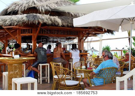 TORREMOLINOS, SPAIN - SEPTEMBER 3, 2008 - Tourists relaxing at a beach bar along the promenade Torremolinos Malaga Province Andalusia Spain Western Europe, September 3, 2008.