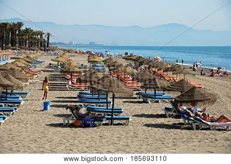 TORREMOLINOS, SPAIN - SEPTEMBER 3, 2008 - Tourists relaxing on the beach with views towards the mountains Torremolinos Malaga Province Andalusia Spain Western Europe, September 3, 2008.