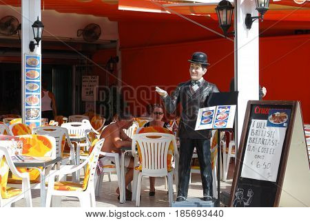 TORREMOLINOS, SPAIN - SEPTEMBER 3, 2008 - Tourists relaxing at a pavement cafe with a statue of Stan Laurel holding a menu Torremolinos Malaga Province Andalusia Spain Western Europe, September 3, 2008.